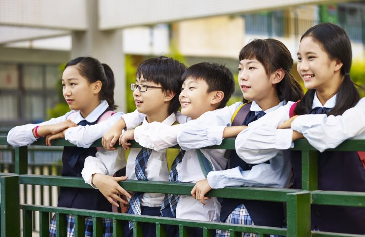 portrait of a group of happy and smiling elementary school students in uniform